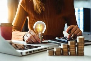 Energy-Saving Tips Conserve Energy Efficiency Importance - woman with bulb