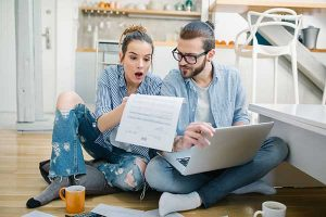 Saving on Electric Bills Tips and Advice for 2021 - image of couple paying bills